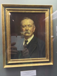 Portrait of Conan Doyle at Sherlock Holmes Museum, Meiringen (with my camera in reflection!)