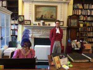 Librarians in regency costume at main desk for 200th anniversary